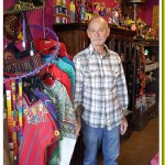 Co-owner of Arte de La Vida James Goodreau poses before a selection of the store's vintage textiles.